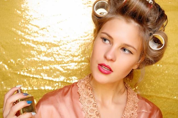 Mooi glimlachend meisje in haarkrulspelden die op goud worden geïsoleerd.