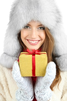Mooi glimlachend meisje in hoed met kerstcadeau op wit wordt geïsoleerd