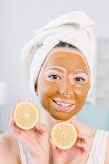 Mooi, glimlachend meisje in witte handdoek en bruin modder gezichtsmasker die pret met twee helften citroen hebben, binnenschot in de witte ruimte