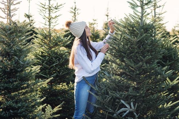 Mooi glimlachend meisje kiest een kerstboom op een plantage voor wintervakantie.