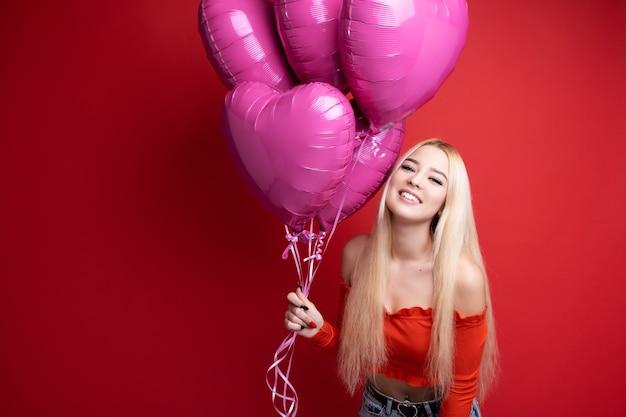 Mooi glimlachend meisje met ballons op rood
