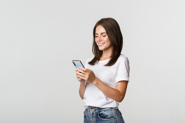 Mooi glimlachend meisje met behulp van mobiele telefoon, smartphone tevreden kijken.