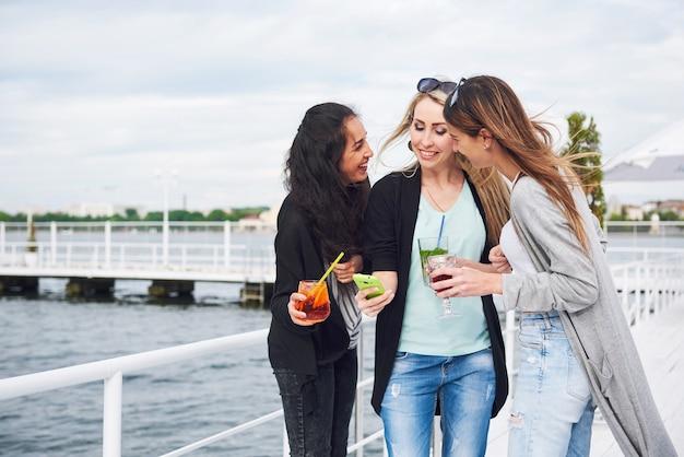 Mooi glimlachend meisje op een pier in de buurt van water. positieve emoties.