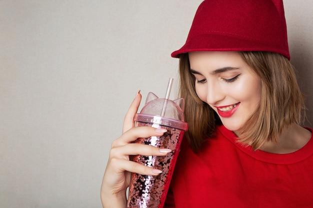Mooi glimlachend model draagt een rode muts en trui en houdt een cocktail vast in de studio. ruimte voor tekst