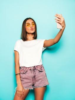 Mooi glimlachend model gekleed in zomer hipster kleding. het sexy onbezorgde meisje stellen in studio dichtbij blauwe muur in jeansborrels. trendy en grappige vrouw nemen selfie zelfportret foto's op smartphone
