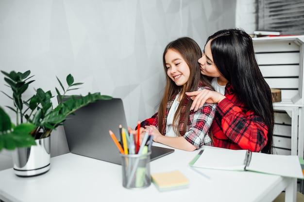 Mooi glimlachend moeder en dochterlezingsnotitieboekje samen thuis