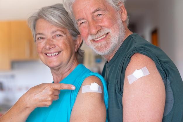Mooi glimlachend oud senior koppel 70s na ontvangst van het coronavirus covid-19-vaccin. positieve mensen thuis