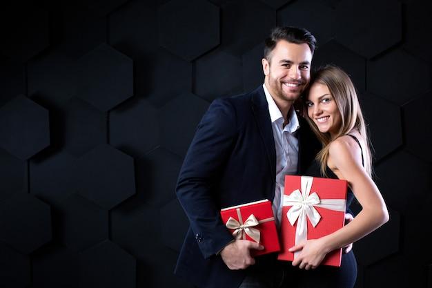 Mooi glimlachend paar met cadeautjes. viering en romantisch concept.