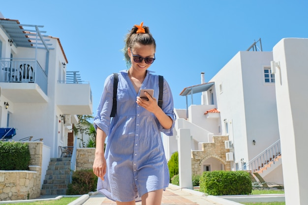 Mooi glimlachend tienermeisje die gebruikend smartphone lopen