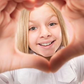 Mooi glimlachend tienermeisje maakt de vorm van een hart met haar handen op de roze achtergrond. gebaar van liefde door vrij jong kind.