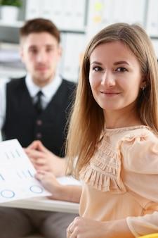 Mooi glimlachend vrolijk meisje op werkplek kijken in de camera met groep collega's