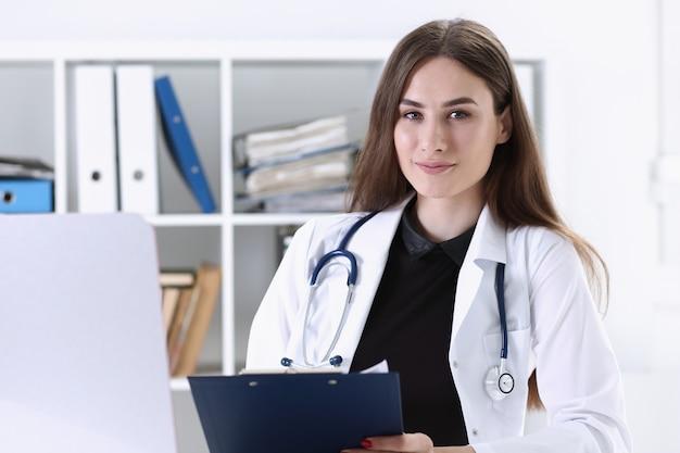Mooi glimlachend vrouwelijk het klembordstootkussen van de artsengreep