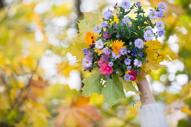 Mooi helder boeket van wilde bloemen in vrouwelijke handen op een kleurrijke herfstachtergrond