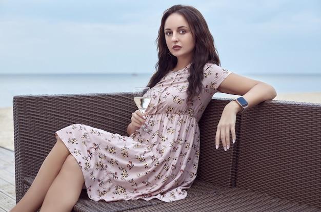 Mooi helder meisje in een zomerjurk zittend op het strand