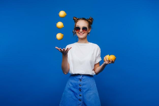 Mooi helder meisje in retro stijl, werpt gele citroenen. blije meid