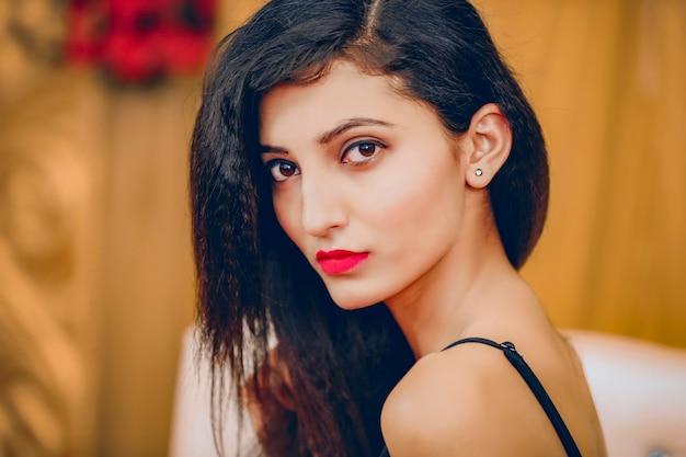 Mooi hete indiase jonge meisjesvrouwenmodel met zwart haar en rode lippen in zwarte westerse jurk