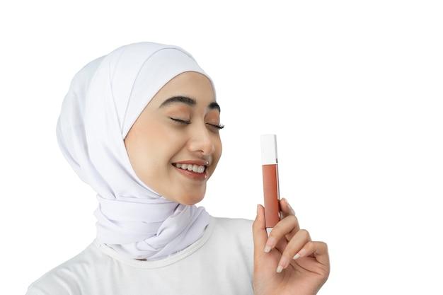 Mooi hijabmeisje die moderne kleding dragen die lippenstiftfles houden