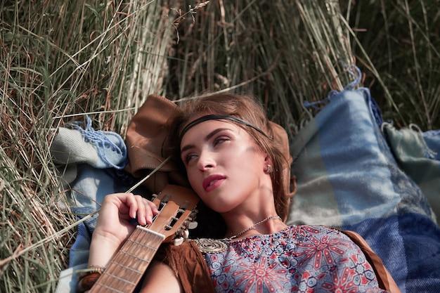 Mooi hippiemeisje dat op het gras ligt