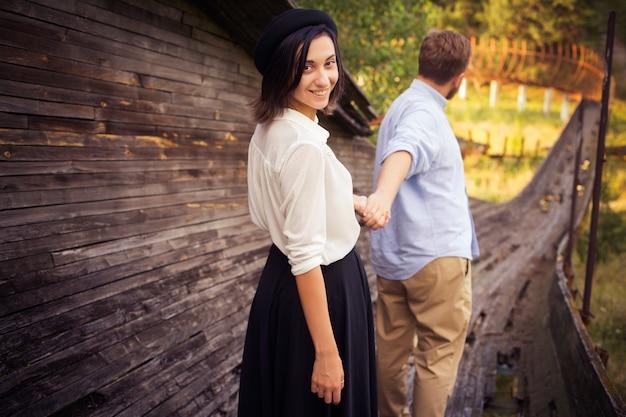 Mooi hipsterpaar in liefde op een datum in openlucht in park die pret hebben. bebaarde roodharige man. donkerbruine vrouw in zwarte rok en witte blouse en zwarte hoed.
