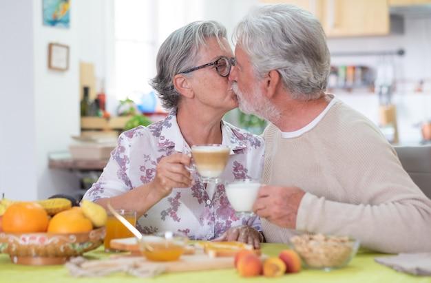 Mooi hoger paar dat thuis ontbijt. goedemorgen met kus. pensioen levensstijl