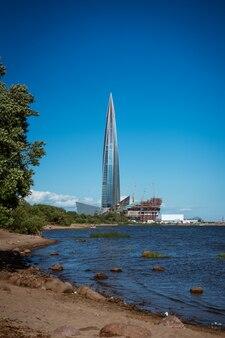Mooi hoog gebouw aan de oever van de baai glazen gevel tegen de blauwe lucht architectuur in de stad the