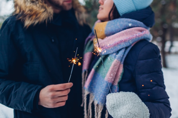 Mooi houdend van paar brandende sterretjes in de winterbos. kerstmis en nieuwjaar concept