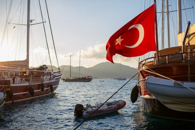 Mooi houten jacht met de grote vlag van turkije op de pier