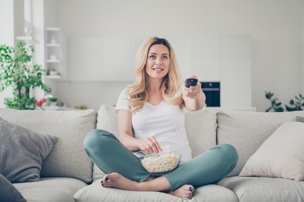 Mooi huiselijk mooie dame zit bank eet popcorn houd afstandsbediening tv kijken