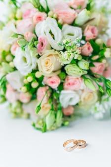 Mooi huwelijksboeket en gouden trouwringen op wit oppervlak