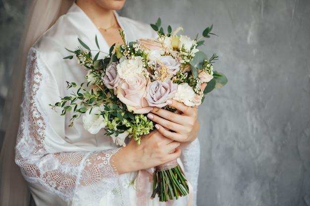 Mooi huwelijksboeket in de handen van de bruid bij de grijze muur op achtergrond.