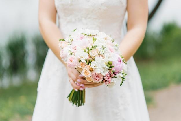 Mooi huwelijksboeket in de handen van een bruid