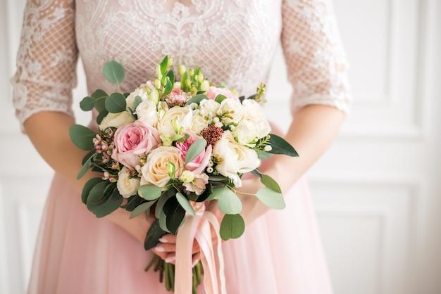 Mooi huwelijksboeket in handen van de bruid. roos, roze en perzik.