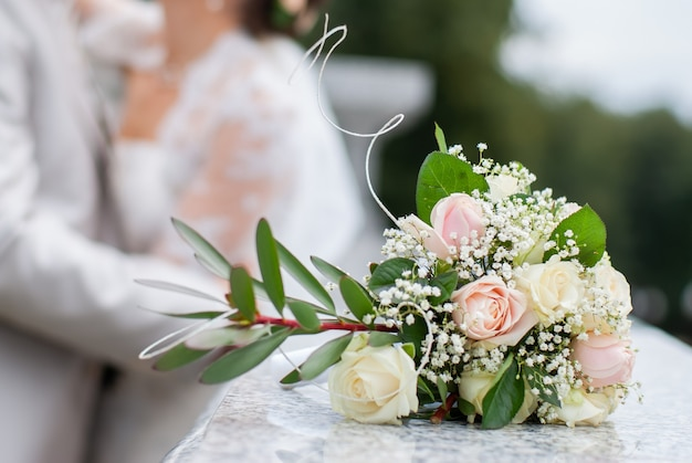 Mooi huwelijksboeket met bruidegom en bruid op achtergrond. net getrouwd stel. stock foto