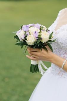 Mooi huwelijksboeket met melkrozen en lila eustoma in handen van de bruid