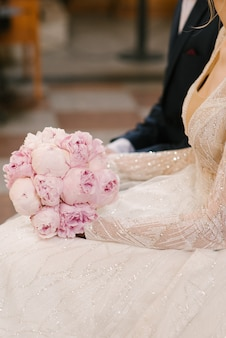 Mooi huwelijksboeket van roze pioenen in de handen van de bruid naast de bruidegom