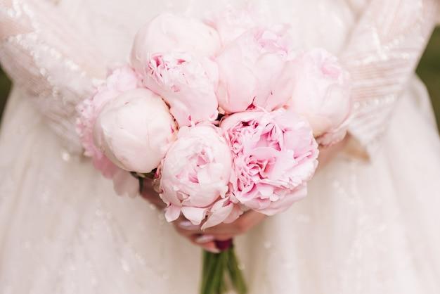 Mooi huwelijksboeket van roze pioenen in de handen van de bruid