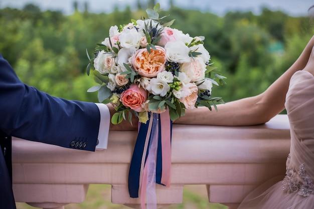 Mooi huwelijksboeket van rozen en pioneert met strepen, met handen op groene achtergrond. huwelijk