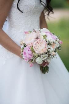 Mooi huwelijksboeket van verschillende bloemen in de handen van de bruid. bruids concept. bos van pioenrozen, rozen, eustoma en groene bladeren
