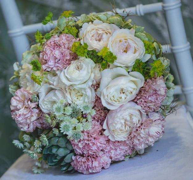 Mooi huwelijksboeket van witte en roze bloemen die zich op een witte stoel bevinden