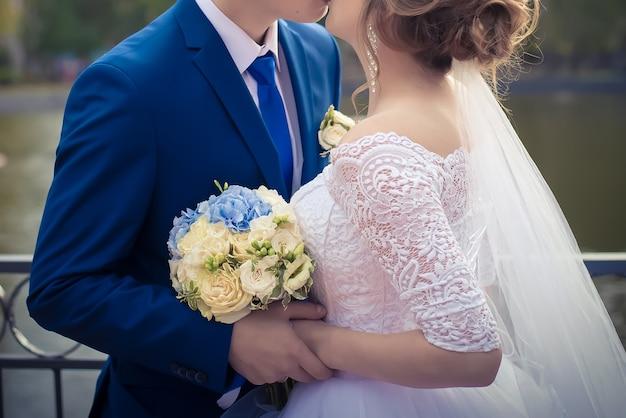 Mooi huwelijksboeket van witte rozen in de handen van de bruid en bruidegom