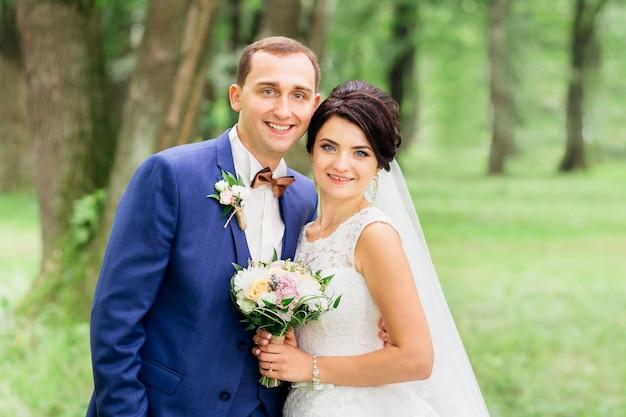 Mooi huwelijkspaar op groene achtergrond die de camera bekijkt
