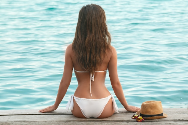 Mooi in de bikini op de houten pier