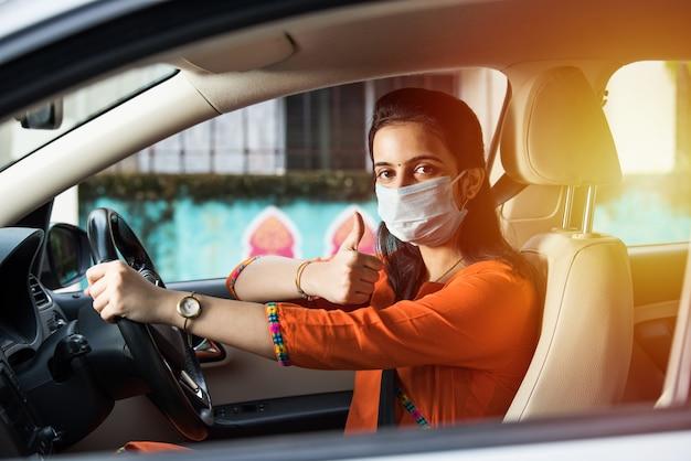 Mooi indiaas jong meisje met een masker zittend in een auto, beschermend masker tegen coronavirus, chauffeur op een stadsstraat tijdens covid-19 pandemie