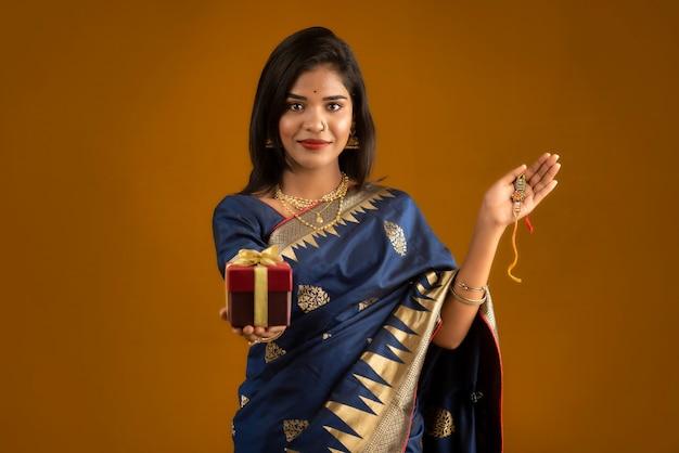 Mooi indiaas meisje toont rakhis en de geschenkdoos ter gelegenheid van raksha bandhan. zuster bindt rakhi vast als symbool van intense liefde voor haar broer.