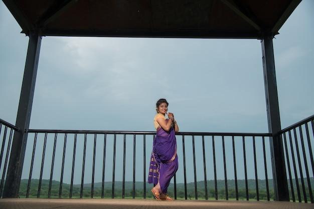 Mooi indisch jong meisje in traditionele saree poseren buitenshuis
