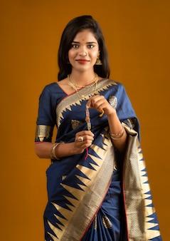 Mooi indisch meisje dat rakhis toont ter gelegenheid van raksha bandhan. zuster bindt rakhi vast als symbool van intense liefde voor haar broer.