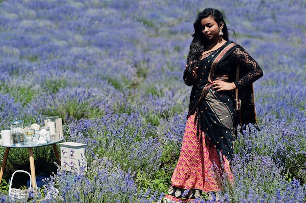 Mooi indisch meisje draagt saree india traditionele kleding in paars lavendelveld.