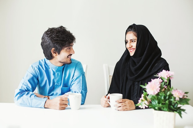 Mooi indisch stel gekleed in moslimkleren pratend over kopje thee