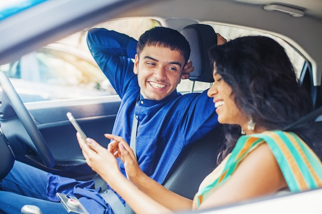 Mooi indisch stel in een auto die mobiele telefoon gebruikt om hun reis online te plannen