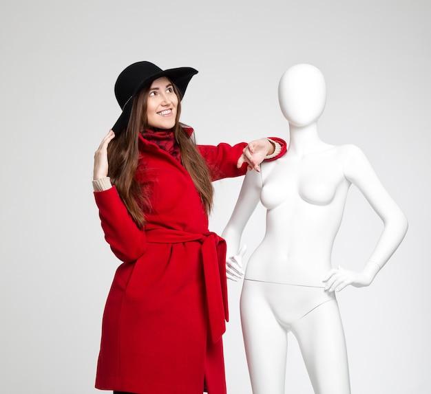 Mooi interessant meisje in de hoed naast de witte vrouwelijke etalagepop op grijze achtergrond